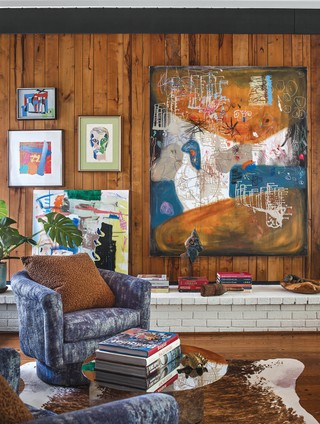 A close-up view of the living room designed by Jessica Davis shows how layering colorful artwork works